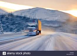 semi truck driving on the snowcovered seward highway at sunrise