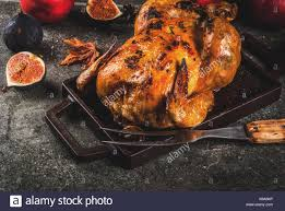 thanksgiving day food roasted whole chicken or turkey on grey