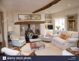 white sofa and pale blue white armchairs around fireplace with