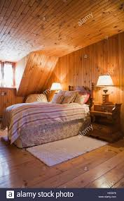 log home interior walls raised single bed in bedroom with knotted pinewood walls in