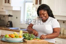 femme qui cuisine overweight preparing vegetables in kitchen stock photo