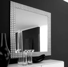 square mirror with silver steel frame placed on the black wall of