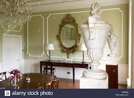 green dining room with large ornamental vases on plinths stock