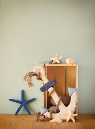 nautical wood anchor and shells on wooden table wooden