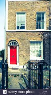 vintage effect split east london terrace home with red door stock