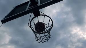 silhouette of ball going through basketball hoop and net in