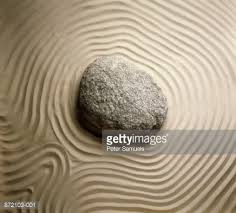 zen buddhist rock garden stone set in raked sand closeup stock