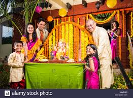 Home Decoration Of Ganesh Festival by Cheerful Indian Family Welcoming Lord Ganesha Idol On Ganesh