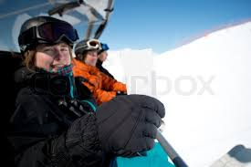 holding blank ski pass while sitting in winter sport chair lift