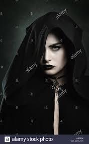 dark portrait of a beautiful vampire woman with black hood stock
