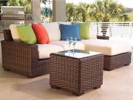 outdoor wicker furniture with red pillows and half round design