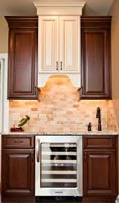 elegant wet bar adjacent to kitchen two tone cabinetry wine