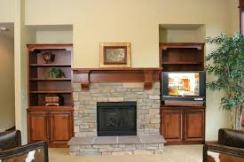 stunning fireplace with stacked stone surround and brown varnished
