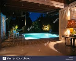 lighting around under lit swimming pool in garden of modern house