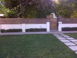 wood and stucco wall just add lush tropical landscaping style