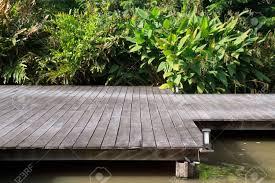 Summer House In Garden - a wooden plank boardwalk on the pond to summerhouse in a garden