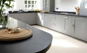 grey kitchen cupboards with black worktop kitchen flooring and worktops wall tiles