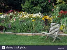Wooden Garden Furniture Rustic Wooden Garden Chair In Front Of Mixed Perennial And Annual