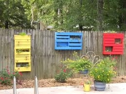 colorful diy hanging planter box on wooden fence in the backyard
