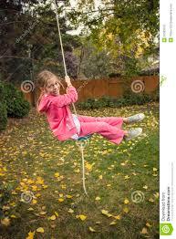 cute playing on a backyard swing outdoors stock photo