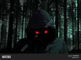 creepy dark man with glowing red eyes in a black forest halloween
