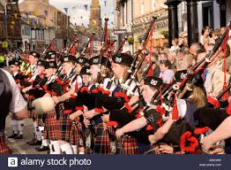 pipe band young kids playing bagpipes on annan high street part of