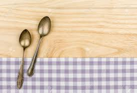 Wooden Kitchen Table Background Two Silver Spoons On A Purple Checkered Table Cloth On A Wooden