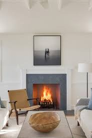 simple white wooden fireplace surround with slate insert to match floors of wet rooms