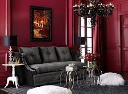 dark red walls and dark grey couch with accents of black and white