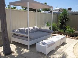 exterior white wooden canopy day bed with grey mattres and
