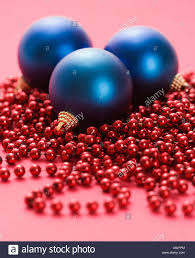 still life of large blue christmas ornaments and strings of red