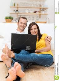 barefoot young couple relaxing with a laptop stock photo image