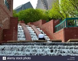 Seeking Houston A Person Seeking Peace Amid Running Waterfall In Downtown Houston