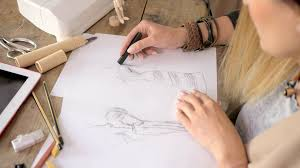 crop faceless shot of young woman drawing sketches of dress while