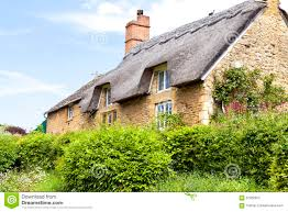 yellow stone english cottage with thatched roof stock photo