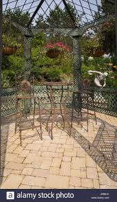 bistro style table and chairs inside gazebo in landscaped backyard