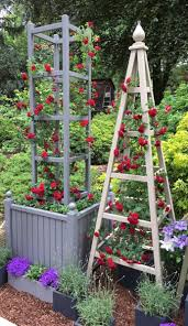 tower obelisk with planter painted deep lead with red roses at rhs