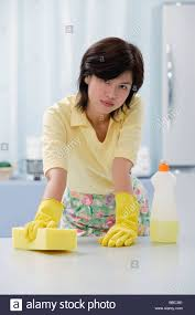 woman in kitchen wearing gloves cleaning kitchen counter with