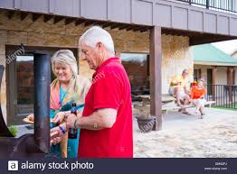 two married couples retired having a backyard barbecue 2 women