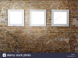 three empty frames on light brick wall blank space posters or art