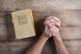 Wooden Desk Background Hands Of Praying Young Man And Bible On A Wooden Desk Background