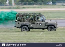 british land rover defender british army landrover speeds off trailing green smoke as part of