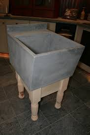 simple concrete cement square laundry sink with wooden base as