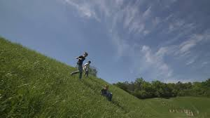 three boys running down the hill and climb up on the other side