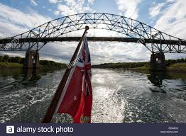 a sailing yacht with a british flag passes the bourne bridge in