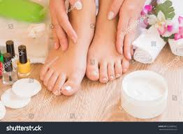 young womans hands applying foot moisturizing stock photo