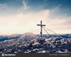 big cross on top of mountain as typical in the alps wooden cross