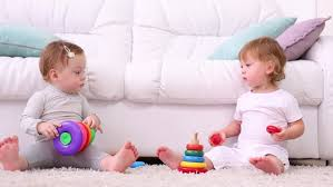 two little kids in dresses sit on white sofa and play with toy