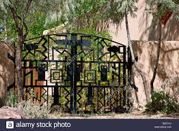 Adobe Style Home A Southwest Style Wrought Iron Gate Closes The Entrance To An