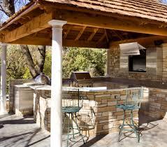 cozy backyard and wood pergola above stone kitchen island and
